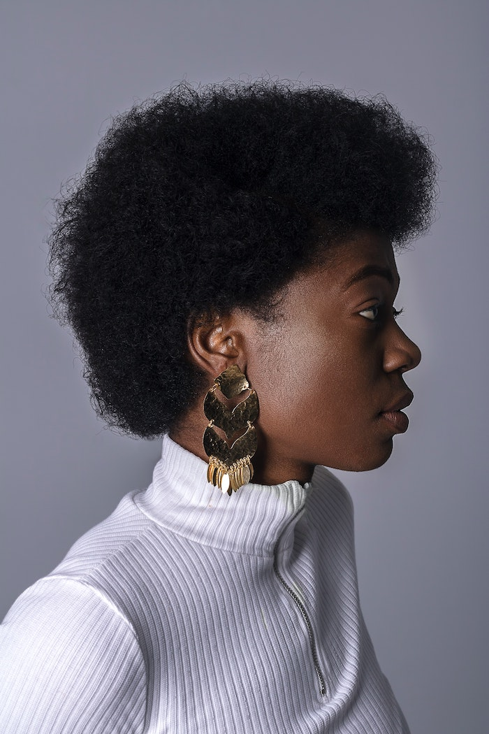 homemade hair mask woman with very short curly hair afro wearing white polo blouse gold earrings
