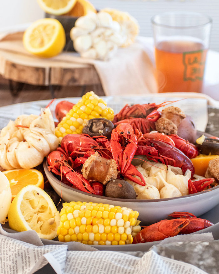 how to make a seafood boil crawfish boil with onion garlic corn on the cob potatoes sausages placed in large bowl