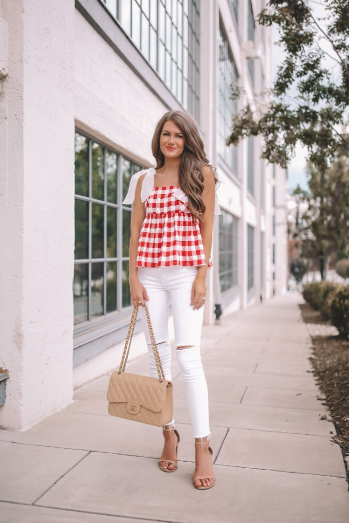 jeans in white with red and white checkered top worn by woman with long hair 4th of july dress nude sandals and bag