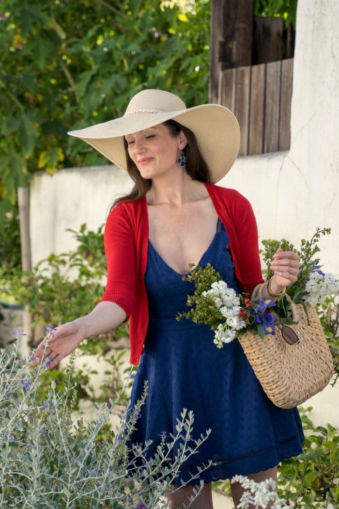 large hat blue dress red sweater 4th of july dress worn by woman with brown hair