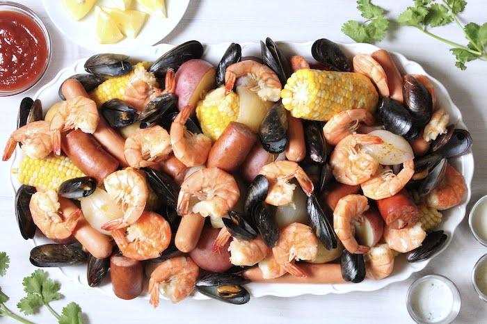 large plate with mussels shrimp sausages crab boil recipe potatoes corn on the cob