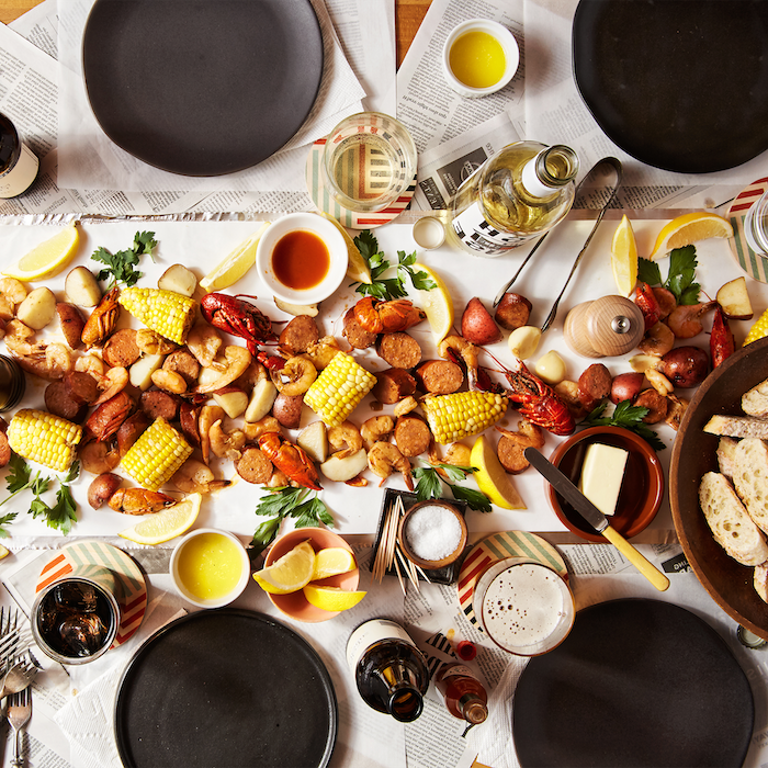 large table with black plates board in the middle shrimp boil recipe corn on the cob potatoes sausages