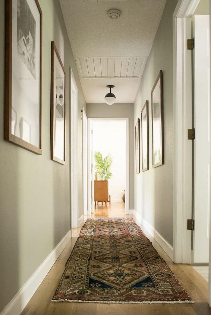 light green walls with framed art on them hallway decor ideas colorful rug on the wooden floor