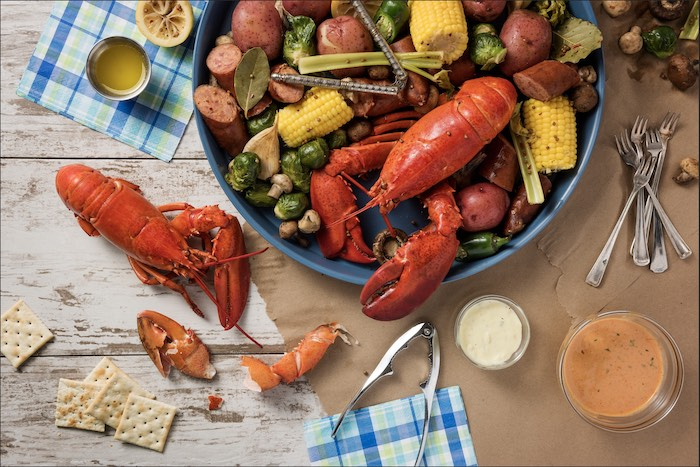 lobster crawfish crab boil recipe placed on white wooden table with potatoes artichoke corn on the cob