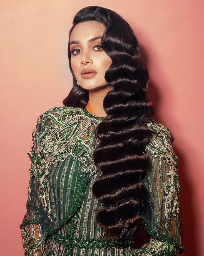 long black hair crimped hair 2021 woman wearing green dress with rhinestones lace photographed on orange background