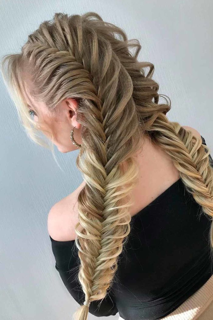 long blonde hair in two messy side buns short crimped hair woman wearing black top