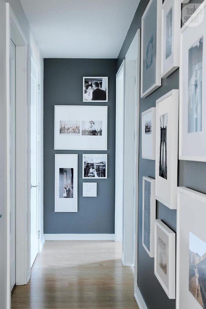 lots of photos and art in white frames of different sizes hanging on dark blue walls narrow hallway ideas