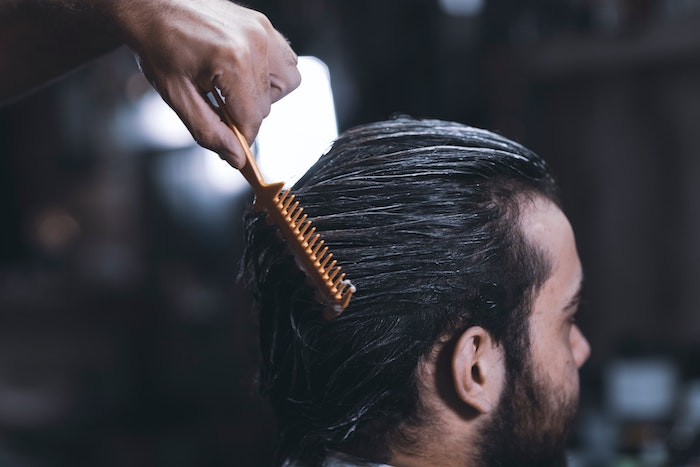 man combing another mans hair with best hair mask for damaged hair black hair beard