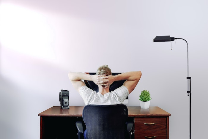man sitting on black office chair in front of desk working from home mac desktop computer on it potted succulent
