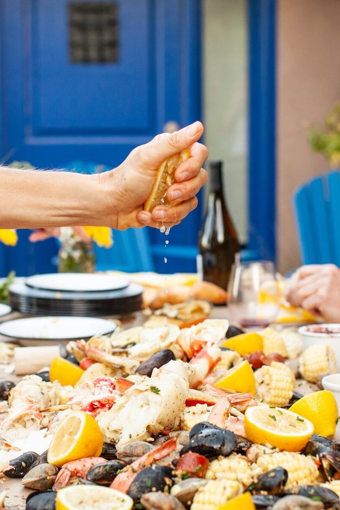 man sqeezing lemon over table with seafood boil in the middle shrimp boil recipe with potatoes corn on the cob
