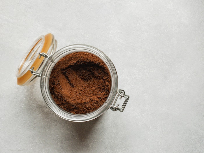 moisturizing hair mask diy jar filled with cocoa powder placed on light gray surface