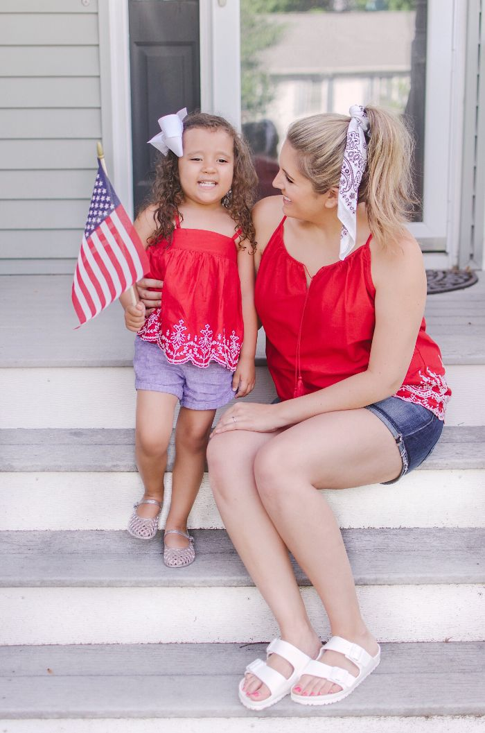 mom and daughter sitting on stairs fourth of july shirts wearing denim shorts red tops