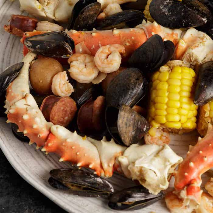 mussels shrimp crab boil seasoning corn potatoes sausages placed on white plate