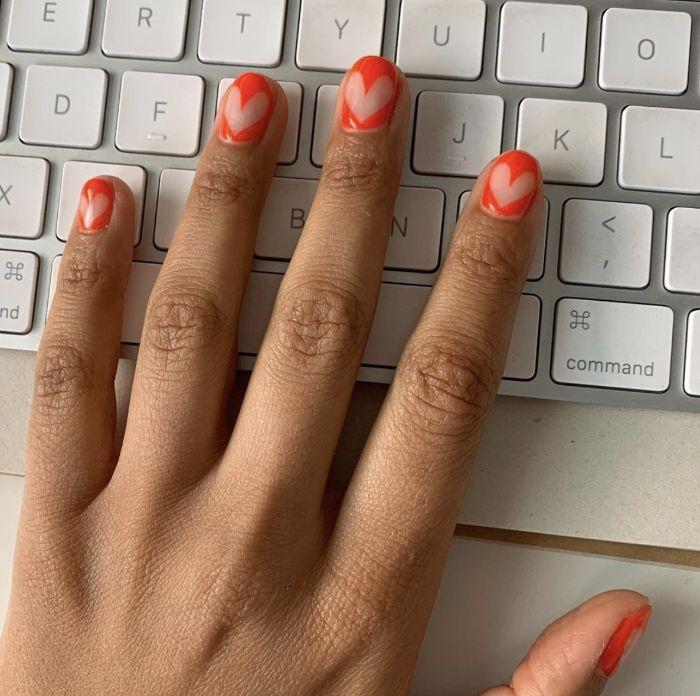 negative space hearts on orange nail polish on short nails gel nail designs