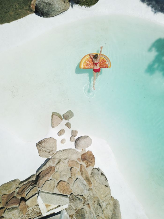 orange slice float woman leaning on it in clear turquoise water beach background images rocks around the water