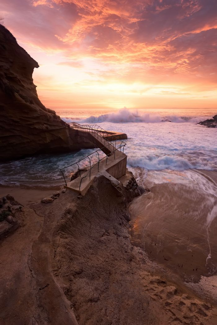 pathway leading around rock summer aesthetic wallpaper waves crashing into the rocks at sunset