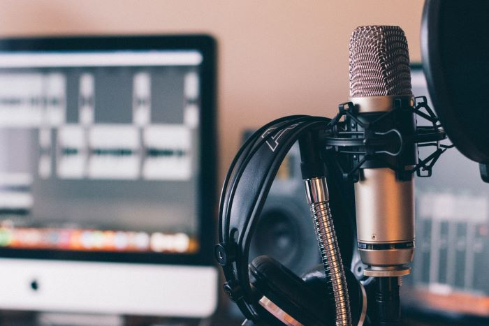 professional microphone with headphones hanging on it lifestyle podcast examples desktop computer in the background