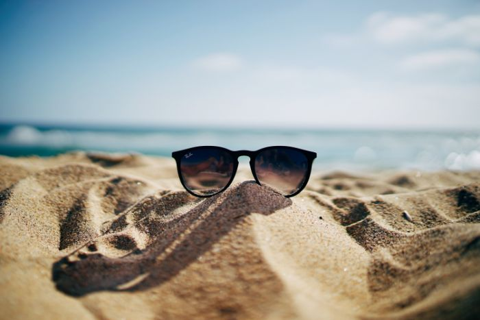 ray ban sunglasses placed on the sand beach aesthetic blurry sky and ocean in the background