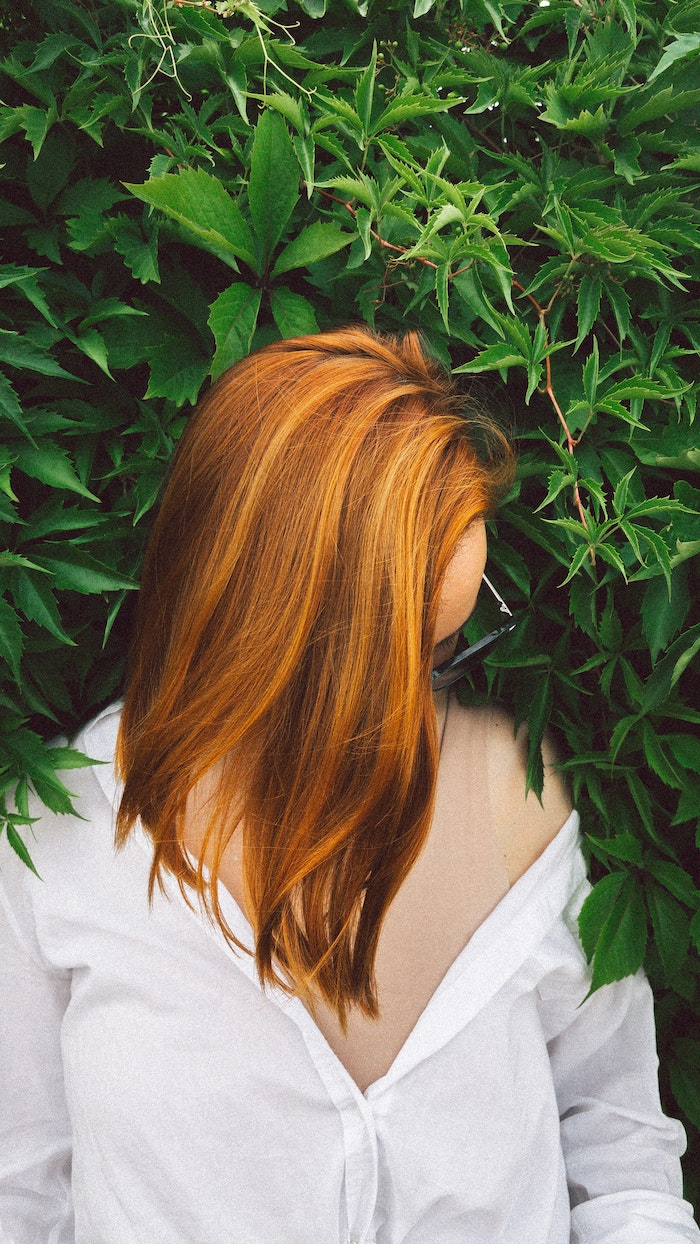 red hair best hair mask woman with medium length straight hair wearing white shirt green bush behind her