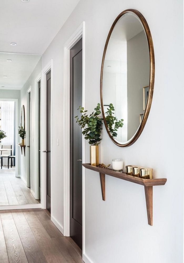 round mirror hanging on white wall above floating shelf hallway wall decor wooden floors and doors