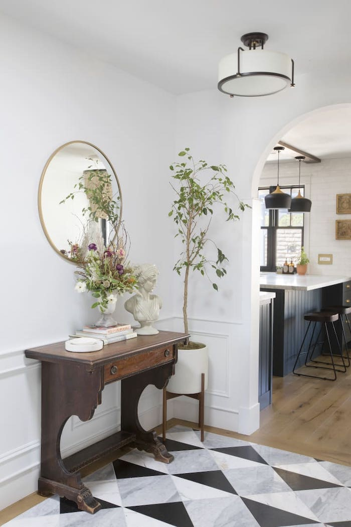 round mirror hanging on white wall above vintage cupboard hallway wall decor ideas gray black and white tiles on the floor