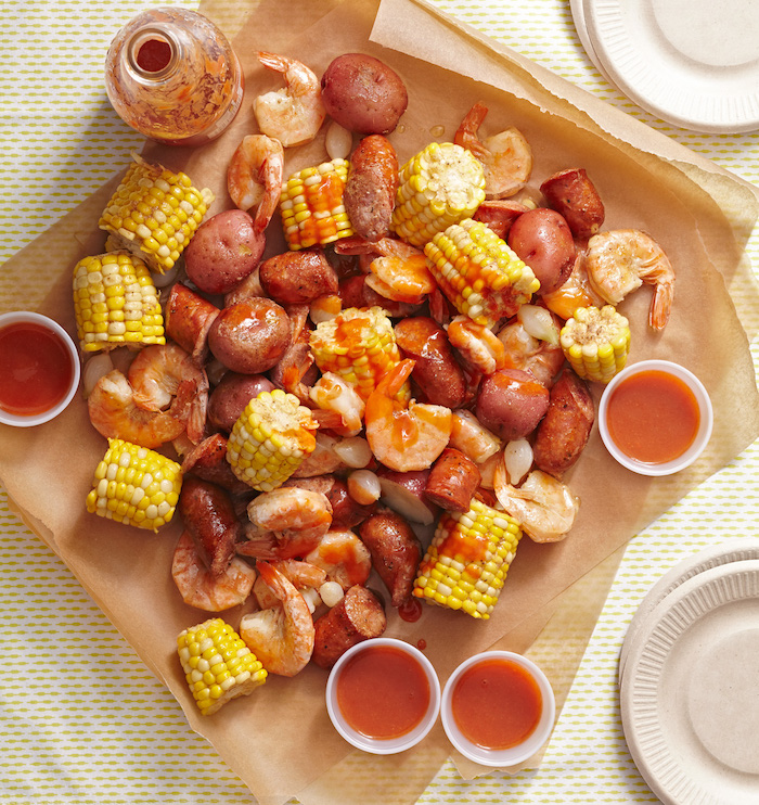sauce in small bowls crab boil recipe corn on the cob sausages potatoes placed on paper lined table