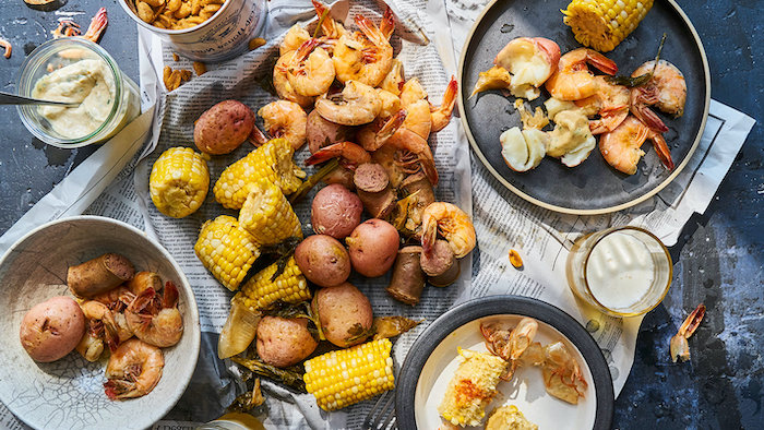 seafood boil recipe table with different plates on it boiled potatoes shrimp corn on the cob