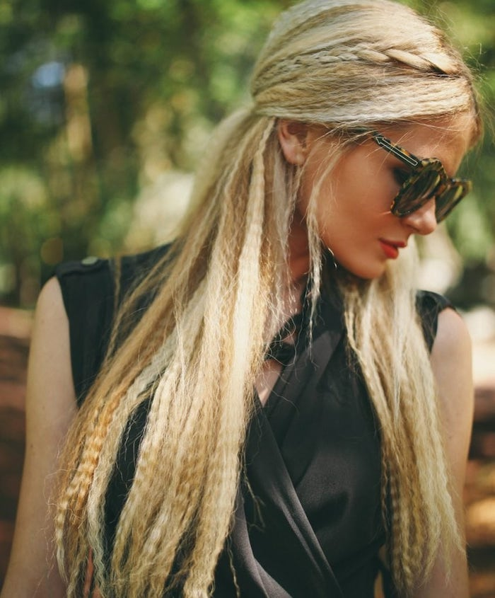 short crimped hair woman with long blonde hair with side braid wearing black top sunglasses