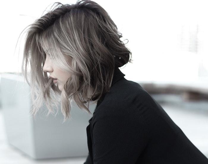 short wavy hair with gray balayage best hair mask for damaged hair woman wearing black shirt