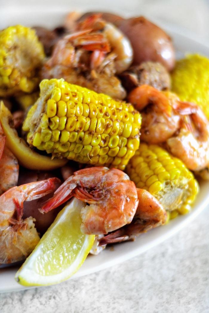 shrimp corn on the cob with lemon wedges placed on white plate shrimp boil recipe