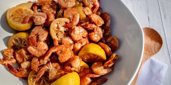 shrimp with lemon wedges seafood boil sauce placed in white bowl placed on white wooden table
