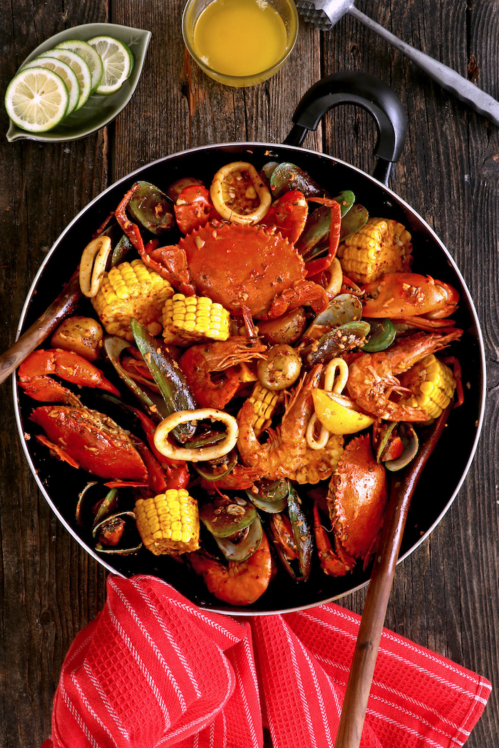 skillet with crabs corn on the cob oysters cajun seafood boil placed on wooden table