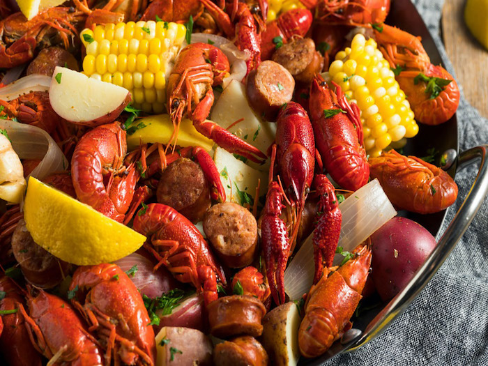 southern crawfish boil with sausages potatoes corn on the cop seafood boil recipe garnished with parsley