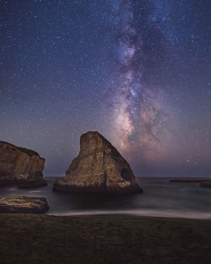 summer aesthetic wallpaper rocks in the water waves crashing into the beach sky with galaxy and stars
