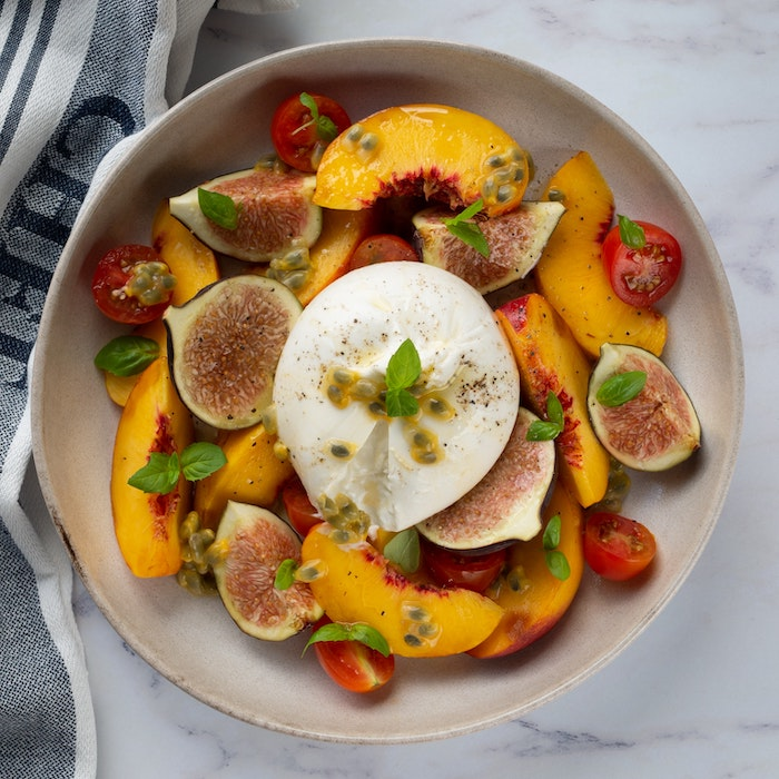 summer salad with peaches figs cherry tomatoes italian burrata cheese fresh basil leaves