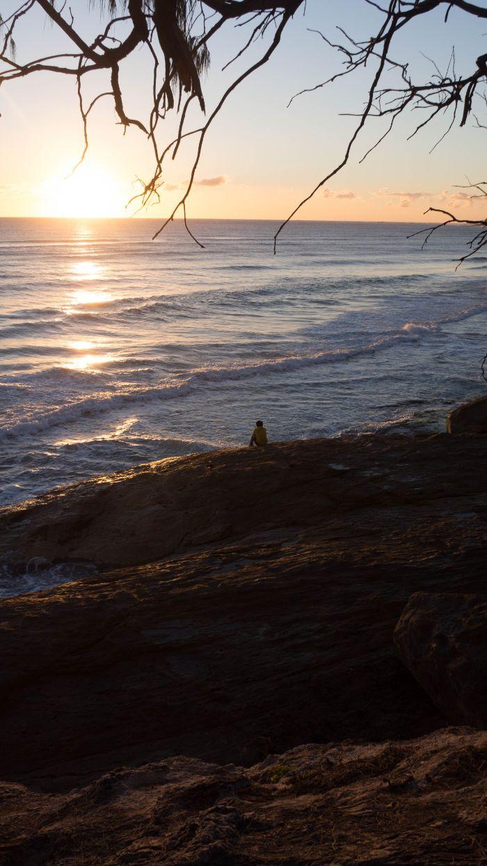 sun rising above the ocean beach background hd man sitting on rocks on the beach watching the sunrise