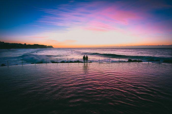 sunset photo beach wallpaper hd man woman standing in infinity pool overlooking the ocean