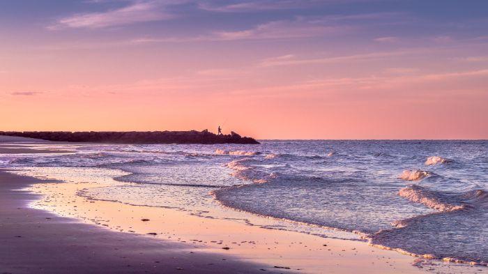 sunset view beach aesthetic wallpaper waves crashing into the beach man standing on rocks