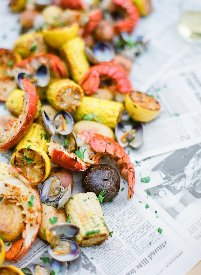 table covered with newspaper pages crab boil recipe corn on the cop potatoes lemon wedges garnished with parsley