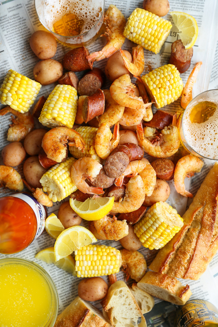table covered with newspaper pages seafood boil sauce shrimp potatoes corn on the cob baguetta lemon wedges