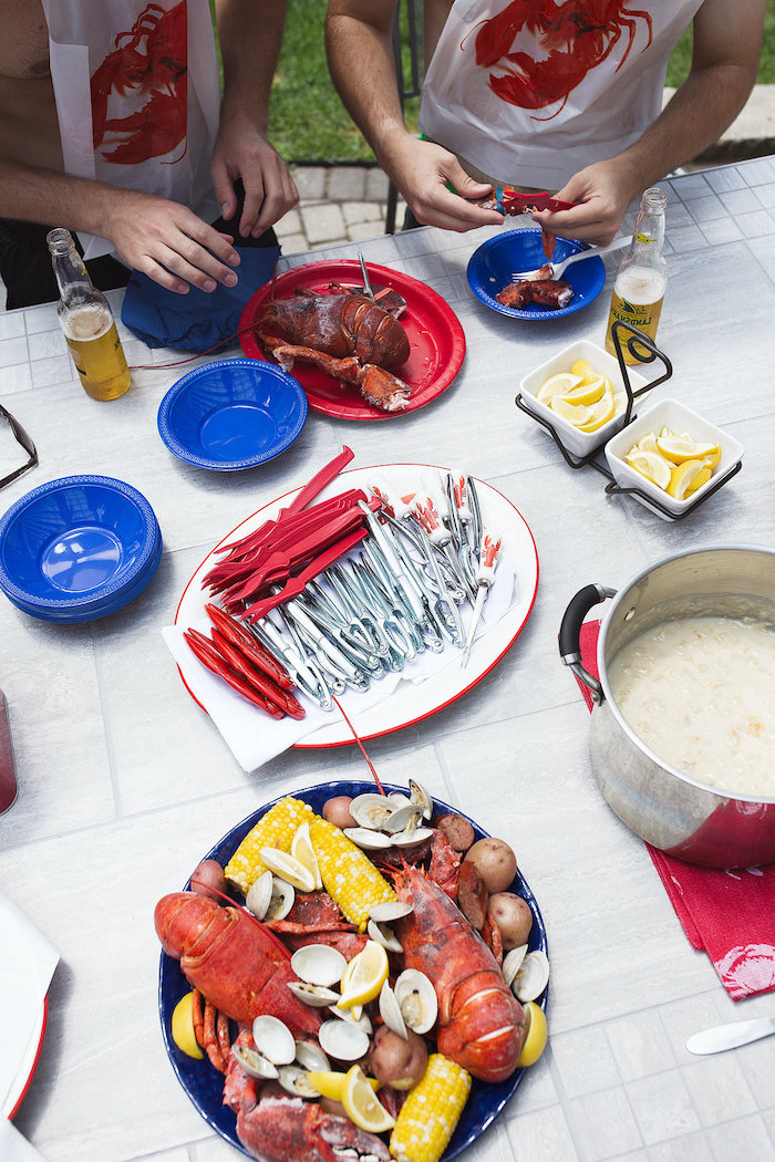 table with different plates and bowls how to boil shrimp lobster boil with potatoes corn on the cob sausages