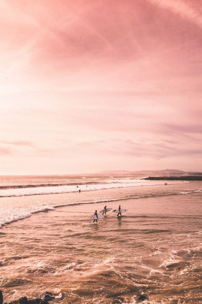 three surfers coming out of the ocean holding surfboards beach desktop wallpaper sunset photo