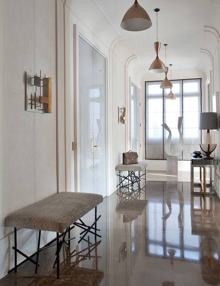 tiled floor with white walls brass light fixtures entryway decor benches along the hallway