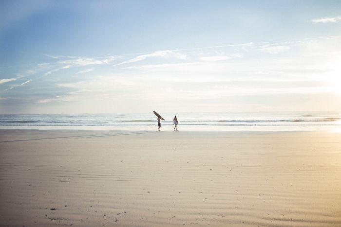 two people one holding surfboard walking on sandy beach beach wallpaper hd ocean in the distance