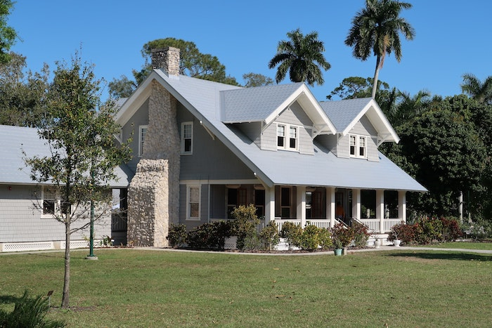 two storey house with a large front porch buying a new home tall palm trees in the backyard
