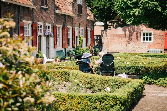 two women sitting on chairs outside talking farmhouse garden table in the backyard