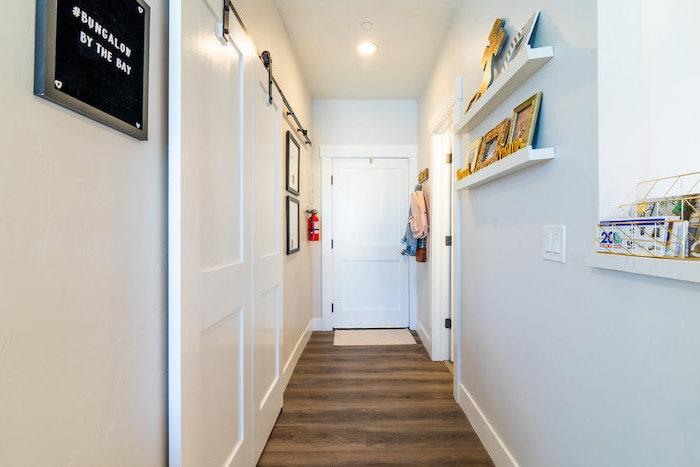 wall mounted shelves on white wall hallway decor ideas photo frames arranged on them wooden floor