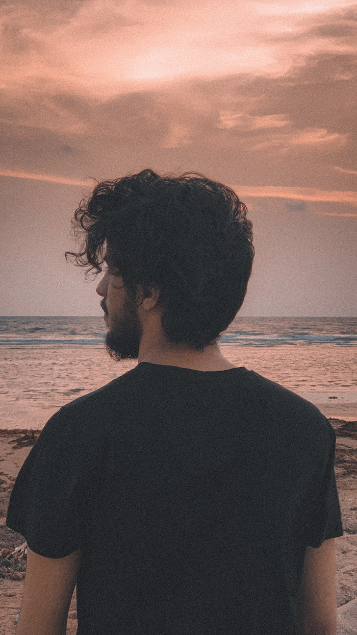 waves in the background best hair mask for damaged hair man standing on the beach with curly black hair wearing black t shirt