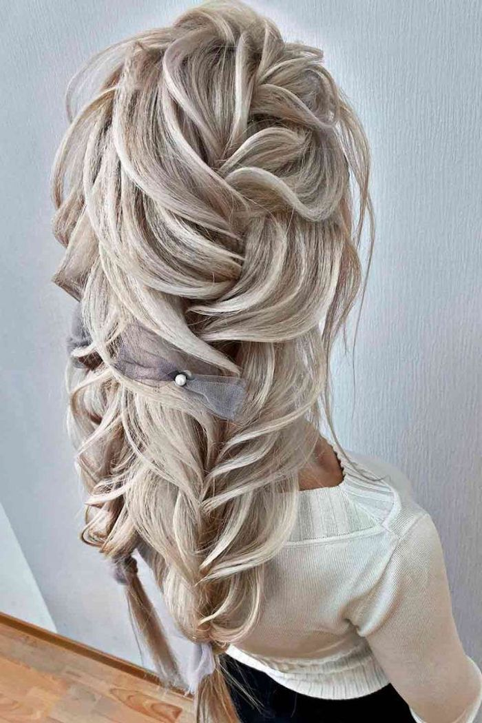 wavy crimped hair woman with very long ash blonde hair in two large messy braids