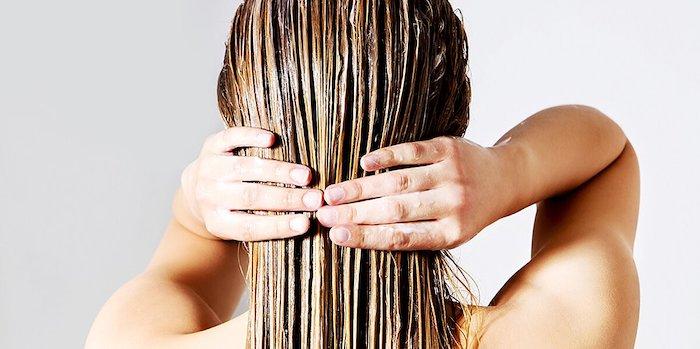 wet hair coconut oil hair mask woman rubbing in coconut oil hair mask into her dark blonde hair